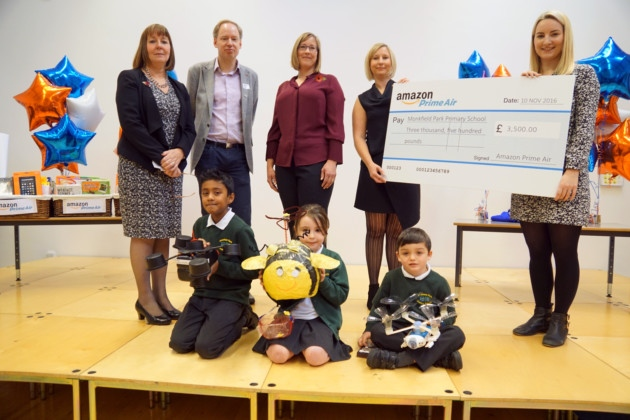 Pupils, from left, Nithyan, Lauren and Olli at Monkfield Park Primary School in Cambourne, with their winning drones. Back, from left, Cambridgeshire County Council chief executive Gillian Beasley, Jonathan Nicholson, of the UK Civil Aviation Authority, Lauren Kisser, of Amazon Prime Air, and headteacher Sarah Jarman with the school's science leader Rebecca Wellings